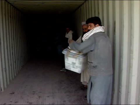 October 2004 Men passing ballot boxes down line inside cargo container at Kandahar Stadium in days immediately following presidential election /...