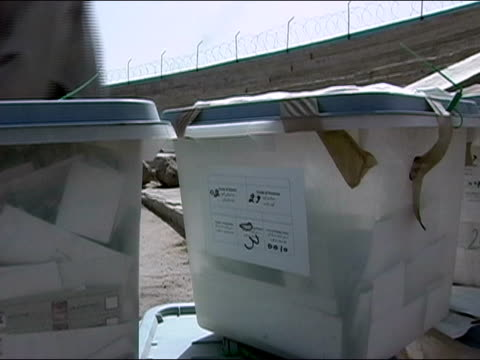 october 2004 men stacking ballot boxes in field at kandahar stadium as ballots start to arrive in days immediately following presidential election /... - operazione enduring freedom video stock e b–roll
