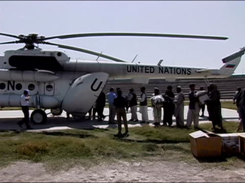 October 2004 Men unloading ballot boxes from UN helicopter at Kandahar Stadium and passing down line as ballots start to arrive for count in days...