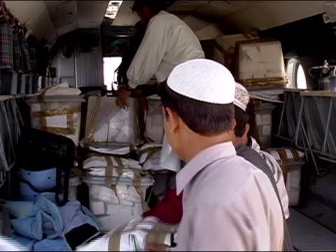 vídeos de stock e filmes b-roll de october 2004 men unloading ballot boxes from un helicopter at kandahar stadium as ballots start to arrive for count in days immediately following... - kandahar