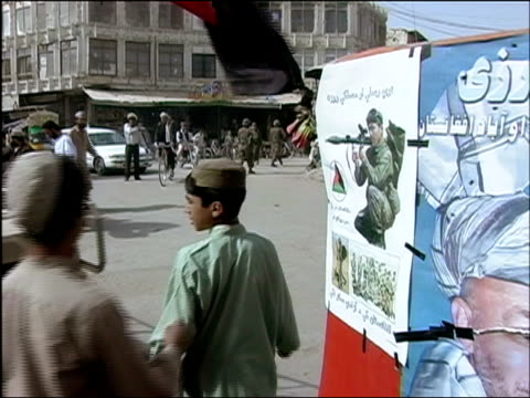 vídeos de stock e filmes b-roll de october 2004 poster on side of street of man firing rocket launcher / boys running alongside us humvee and troops from afghan national army and... - kandahar