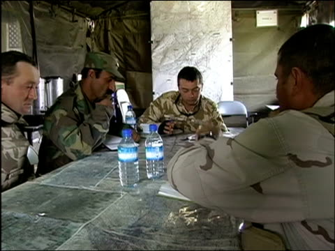 October 2004 Romanian military Embedded Training Team officers and Afghan National Army officers going over intelligence with US military officer in...