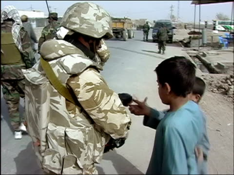 october 2004 soldier from romanian embedded training team giving candy to two boys during joint patrol with troops from afghan national army in days... - afghan national army stock videos and b-roll footage