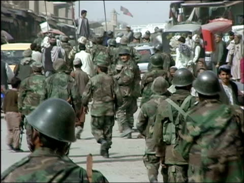 October 2004 Troops from Afghan National Army and Romanian Embedded Training Team walking down street during joint patrol led by US military in days...