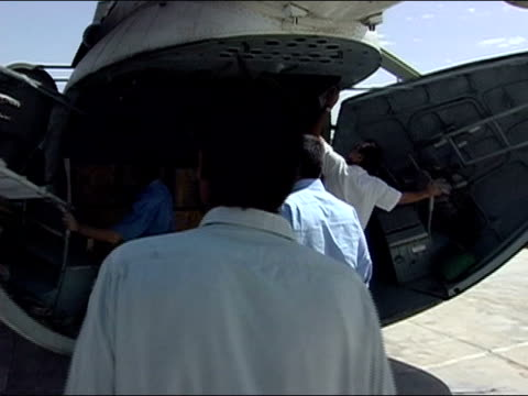 October 2004 UN workers and pilots opening doors to helicopter containing ballots at Kandahar Stadium as ballots start to arrive for count in days...