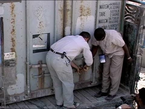 vídeos de stock e filmes b-roll de october 2004 / un workers unlocking doors to cargo container on truck containing ballot boxes at kandahar stadium as ballots start to arrive in days... - kandahar