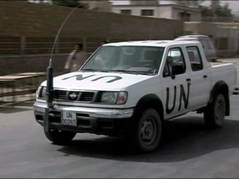 October 2004 United Nations pickup truck pulling up to gate at Kandahar Stadium in days immediately following presidential election / security guard...