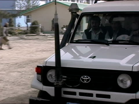october 2004 united nations vehicle followed by security escort leaving polling station with ballot boxes at close of presidential election / driver... - kandahar stock-videos und b-roll-filmmaterial