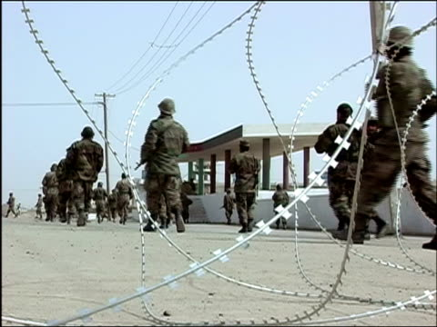 October 2004 View through barbed wire outside Romanian military compound in Kandahar of Afghan National Army troops leaving for USled joint patrol...