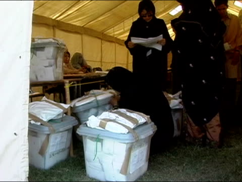 October 2004 Women organizing ballot boxes inside tent at Kandahar Stadium as ballots start to arrive for count in days immediately following...