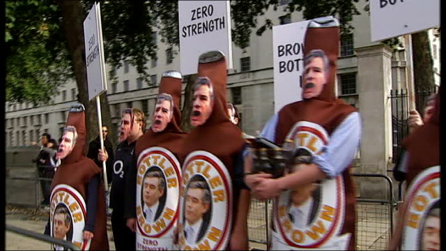 london: whitehall: conservative activists with placards and dressed as brown bottles with face of gordon brown and 'bottler brown' logo singing '... - gordon brown stock-videos und b-roll-filmmaterial