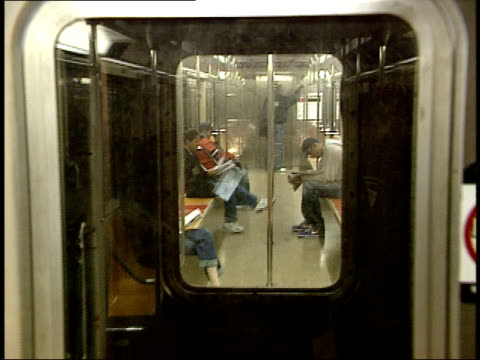 october 21, 2004 passengers sitting on a new york city subway train, viewed through the door / new york, united states - bahnreisender stock-videos und b-roll-filmmaterial
