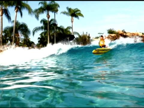 october 21, 2009 a surfer long boarding a wave park - 屋外遊具点の映像素材/bロール