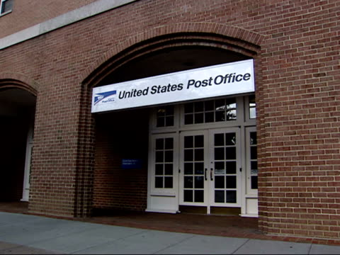 October 23 2001 WS Exterior brick building archway with hanging sign reading United States Post Office above door and pedestrians walking past /...
