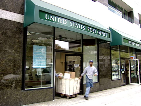 October 23 2001 PAN Exterior of United States Post Office with postal worker rolling out mail cart and pedestrians walking past / Washington DC...