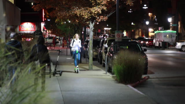 a lime scooter rider zips along a sidewalk on kirkwood avenue in bloomington indiana the scooters arrived several weeks ago in bloomington by the... - lime stock videos & royalty-free footage