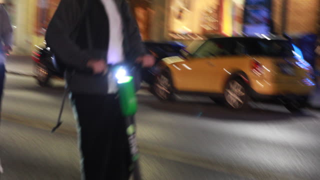 lime scooter riders zip down kirkwood avenue in bloomington indiana the scooters arrived several weeks ago in bloomington by the hundreds and are now... - motorino video stock e b–roll