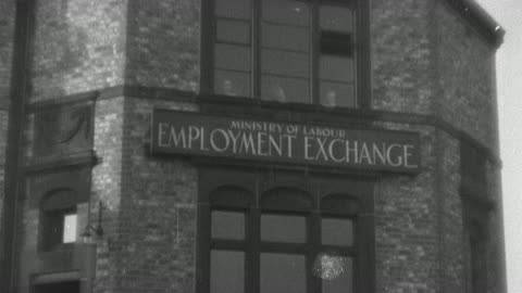 stockvideo's en b-roll-footage met october 29, 1929 montage factory production grinding to a halt and workers standing in line at the employment office as the stock market crashes / london, england - werkloosheid