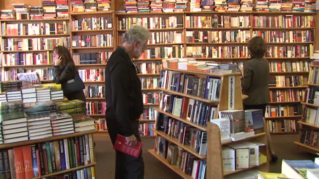 october 29 2009 montage shoppers perusing books in bookstore filled with stocked shelves and stacks on tables / washington dc united states - bokhandel bildbanksvideor och videomaterial från bakom kulisserna