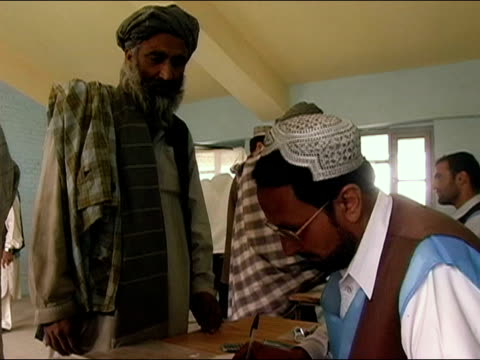 vídeos de stock e filmes b-roll de october 9 2004 election worker checking men's identification cards at polling station on election day / kandahar afghanistan / audio - kandahar