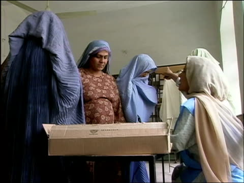 vídeos de stock e filmes b-roll de october 9 2004 election worker handing woman ballot and giving instructions / kandahar afghanistan / audio - kandahar