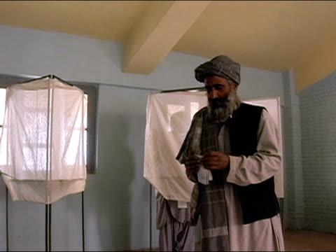 vídeos de stock e filmes b-roll de october 9 2004 man leaving voting booth with ballot / placing slip in box stuffed with ballots / tilt down to medium shot of ballot box / kandahar... - kandahar