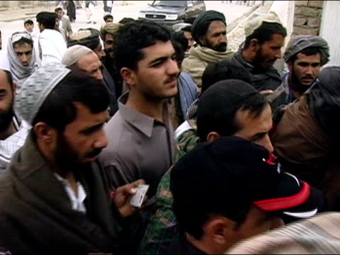 october 9 2004 men impatiently moving through line outside polling station to vote in presidential election / soldiers checking men's id cards /... - baseballmütze stock-videos und b-roll-filmmaterial