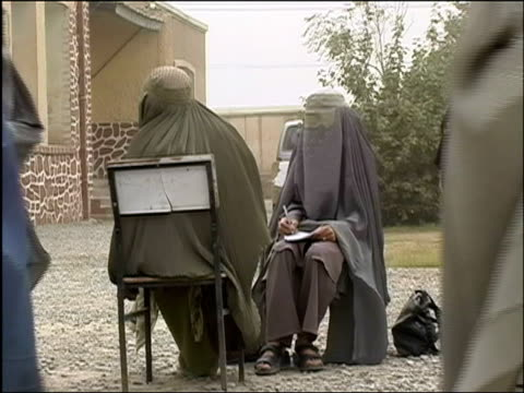 october 9, 2004 women in burqas registering to vote at polling station on election day as other women come and go / kandahar, afghanistan / audio - documentary footage stock videos & royalty-free footage