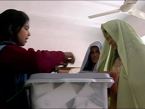 October 9 2004 Women placing ballots in stuffed ballot box in presidential election / Kandahar Afghanistan / AUDIO