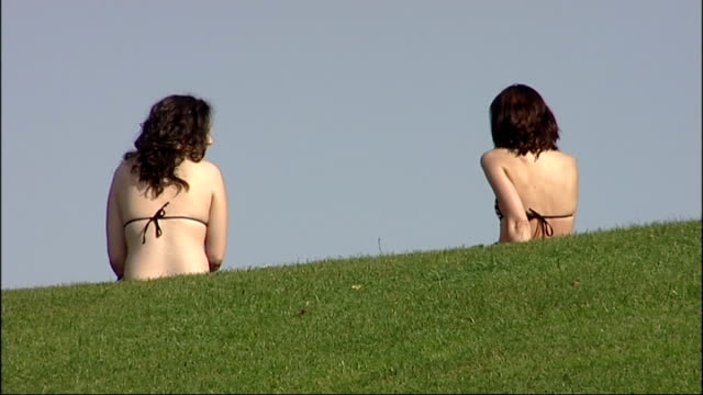 October heatwave in Britain Back view two women wearing bikinis sitting on grass in park Group of people sunbathing in park Man playing guitar in park