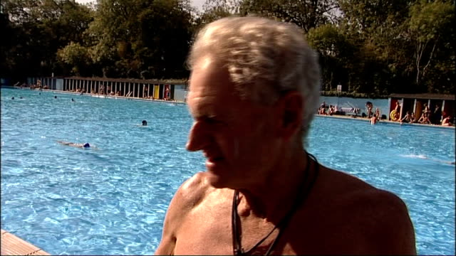 vídeos y material grabado en eventos de stock de south london tooting bec lido ext man diving into outdoor swimming pool shots of people enjoying the hot sunshine around pool woman in pool smiling... - vox populi