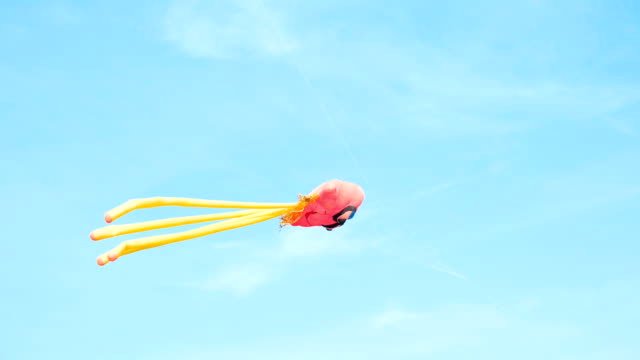 octopus-like kite flying in the blue sky - kite toy stock videos and b-roll footage
