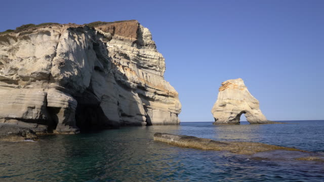 odd rock formations jut from sea off coast of greek islands - natural arch stock videos & royalty-free footage
