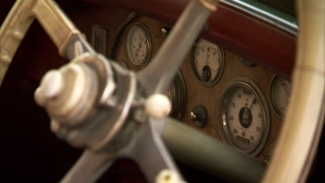 Odometers and a steering wheel cover the dash board of a classic car in India.