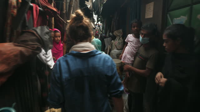 of 2 - shows exterior shots narrow alleyways in the slum of kallyanpur, poverty in evidence, children in the street, people trying to brush away... - changing lightbulb stock videos & royalty-free footage