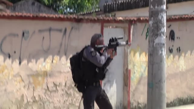 vídeos de stock e filmes b-roll de shows exterior shots armed police officers from the core unit carrying out an operation in the alamo favela in rio de janeiro sounds of gunfire and... - bairro de lata