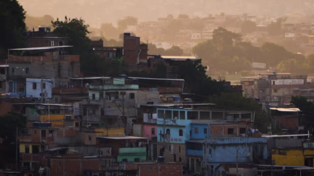 vídeos de stock e filmes b-roll de shows exterior shots rooftops of a favela in rio de janeiro and people walking along the streets and exterior and interior shots children who attend... - favela