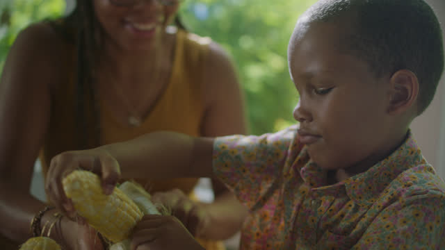 MCU of a little boy shucking corn with a young woman