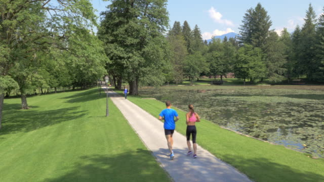 AERIAL of a man and a woman running in the park along a lake