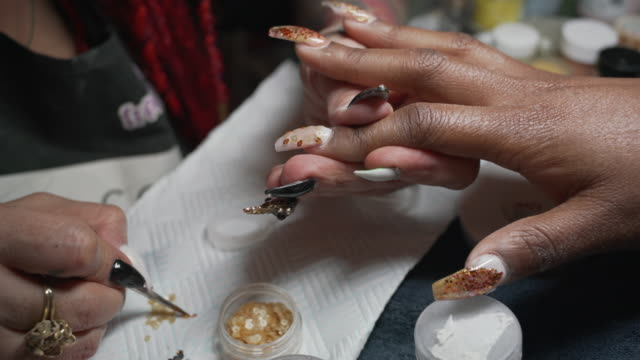 PART TWO of a short film about a nail artist working on a clients hands in a nail studio.