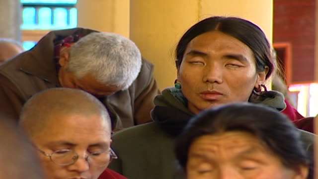 of a tibetan worshipper, his eyes rolled and half open to the back of his head, listening to hh dalai lama giving a sermon at tsuglagkhang temple. - worshipper stock videos & royalty-free footage