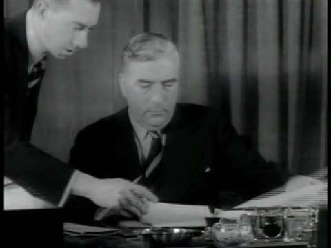 Sign Prime Minister MS Rt Hon Sir Robert Menzies w/ papers at desk Sign Opposition Party Leader MS John Curtain sitting at desk w/ woman next to desk