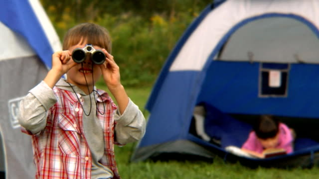 ms portrait of boy looking through binoculars as girl reads in tent/ bovina, new york - canocchiale video stock e b–roll