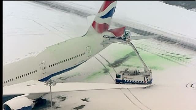 air view / aerial of british airways plane covered in snow on wings and maintenance truck trying to clean the tail wing - tail wing stock videos and b-roll footage