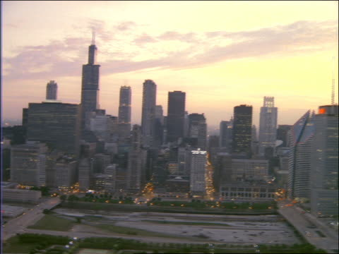 aerial of chicago skyline + city at sunset / tilt down to fountain - レガッタリグレービル点の映像素材/bロール