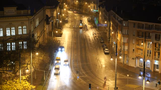 4k tl of city centre traffic in traditional european city at night in the town of szeged hungary - セゲド点の映像素材/bロール