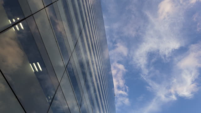TL of cloud reflection on office building under blue sky in financial district