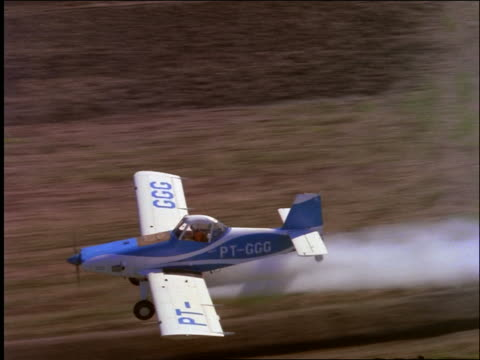 aerial of crop duster flying over farm fields / brazil - crop sprayer stock videos and b-roll footage