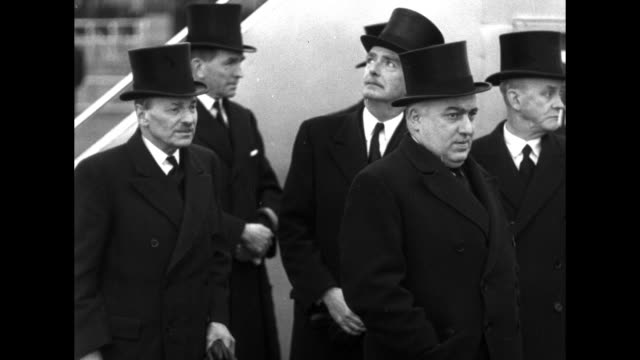 vídeos de stock, filmes e b-roll de of dignitaries in top hats gathered on the tarmac at london airport / vs winston churchill walks using cane, wearing hat and coat with another / vs... - artigo de vestuário para cabeça