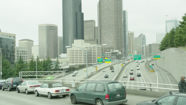 h-d (shot from overpass) of downtown seattle freeway traffic, pan l to black audi r-b l-r  to and by camera at end of shot - downtown stock videos & royalty-free footage